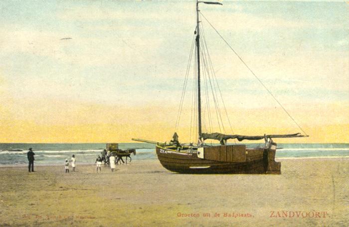 Een boot op het strand van Zandvoort met spelende kinderen erbij.
